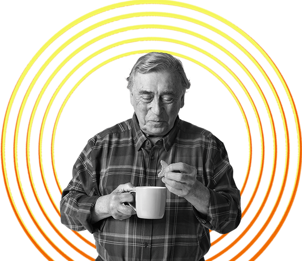 Older man with a cup of tea in his hand and a biscuit hero image