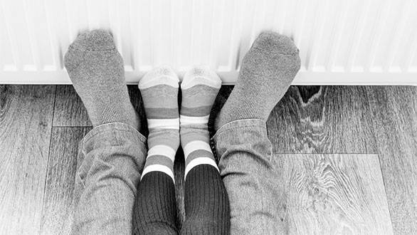 An adult and child warming their feet against radiator - Sainsbury's energy offers a warm home discount